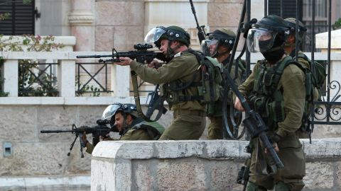 Israeli soldiers aim their weapons toward Palestinian protesters during clashes in Bethlehem on October 12.