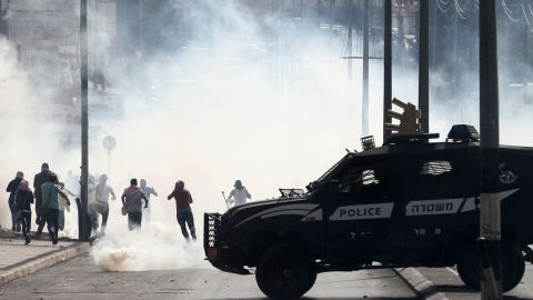 An Israeli police vehicle drives in front of Palestinian protesters in Bethlehem on October 13.