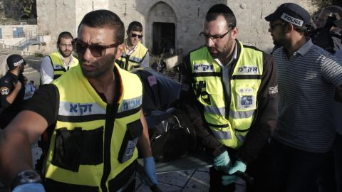 """Israeli Zaka volunteers carry the body of a man who attempted to carry out a knife attack and was shot by Israeli police, at the Damascus Gate at the entrance of the Old City in east Jerusalem on October 14, 2015. Israeli police said a """"terrorist"""" attempted to stab a security guard at an entrance to Jerusalem's Old City but was shot before harming anyone, the latest in a wave of such incidents. AFP PHOTO / AHMAD GHARABLI        (Photo credit should read AHMAD GHARABLI/AFP/Getty Images)"""