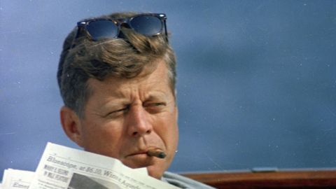 Kennedy reads the newspaper aboard the presidential yacht Honey Fitz off the coast of Hyannis Port, Massachusetts.