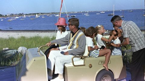 Kennedy steers a golf cart in Hyannis Port, Massachusetts, with Jacqueline, Maria Shriver, Sydney Lawford, Tim Shriver and John Jr.