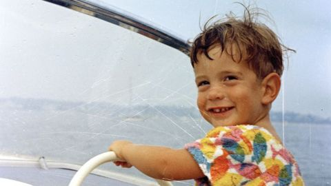 John Jr. smiles at the wheel of a boat off the coast of Hyannis Port, Massachusetts.