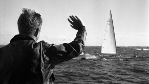 """President John F. Kennedy waves to the crew of the yacht, """"Weatherly"""" (of the New York Yacht Club), while watching the first race of the 1962 America's Cup aboard the USS Joseph P. Kennedy, Jr., off the coast of Newport, Rhode Island."""