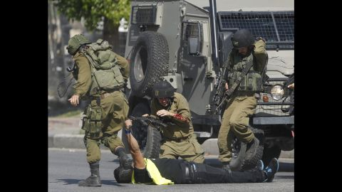 """An Israeli soldier runs to help another who was just stabbed by an alleged Palestinian assailant, seen on the ground holding a knife, during clashes in Hebron, West Bank, on Friday, October 16. In recent weeks, there has been a spike in violence across Israel and the Palestinian territories. <a href=""""http://www.cnn.com/2015/10/14/middleeast/israel-palestinians-violence-explainer/index.html"""" target=""""_blank"""">Why now? CNN's Ben Wedeman breaks down the issues</a>"""