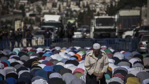 Palestinians kneel during noon prayers in Jerusalem on October 16.