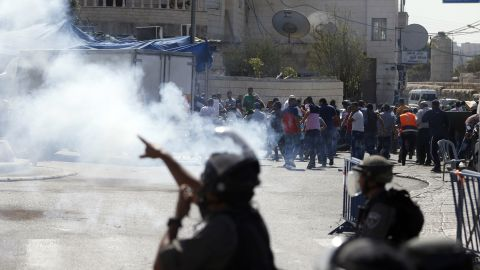 """Israeli security forces fire tear gas canisters and stun grenades towards Palestinian protesters after the Friday prayers in the Ras al-Amud neighbourhood in east Jerusalem, on October 16, 2015. Palestinians called for a """"Friday of revolution"""" against Israel, and Jerusalem police barred men under 40 from attending the main weekly prayers at the flashpoint Al-Aqsa mosque, seeking to keep young protesters away."""