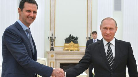 """Russian President Vladimir Putin (R) shakes hands with his Syrian counterpart Bashar al-Assad (L) during a meeting at the Kremlin in Moscow on October 21, 2015. Assad, on his first foreign visit since Syria's war broke out, told his main backer and counterpart Putin in Moscow that Russia's campaign in Syria has helped contain """"terrorism"""". AFP PHOTO / RIA NOVOSTI / KREMLIN POOL / ALEXEY DRUZHININ        (Photo credit should read ALEXEY DRUZHININ/AFP/Getty Images)"""