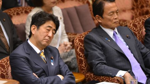 """Japanese Prime Minister Shinzo Abe (L) and Finance Minister Taro Aso """"listen"""" to a question from an opposition lawmaker during a budget session at the National Diet in Tokyo in February 2013."""