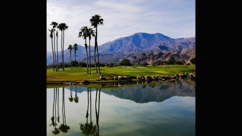 """At this course, you would be forgiven for deliberately aiming your ball towards the water hazard. The still, crystal water creates the perfect canvas to mirror the backdrop of palm trees and mountains. <a href=""""https://instagram.com/channingbenjaminphotography/"""" target=""""_blank"""" target=""""_blank"""">@channingbenjaminphotography</a> described it as: """"The best!"""""""