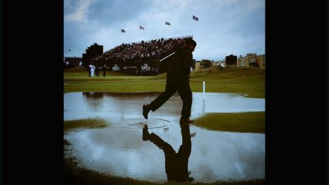 """CNN's <a href=""""https://instagram.com/murpho2005/"""" target=""""_blank"""" target=""""_blank"""">Chris Murphy </a>captured this shot at St. Andrews soon after the deluge. The gray skies and man skipping through the puddle illustrate just how quickly the rain fell and waterlogged the course. """"A tad wet at St Andrews on Friday. All adds to the fun, when you're sitting in the warm & toasty media center anyway,"""" he said."""