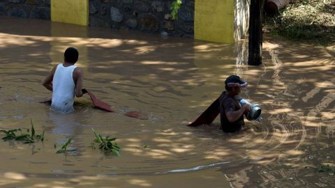 Firefighters set a line to pump water out from a flooded area in Cihuatlan, Mexico, on October 24.