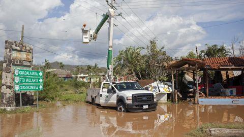 Men work to restore downed power lines on October 24 in Melaque.