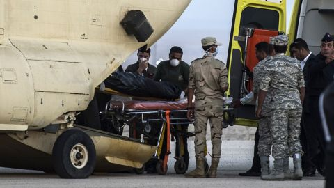 Egyptian paramedics load the bodies of victims into a military plane at a military air base by the Suez Canal on Saturday, October 31.