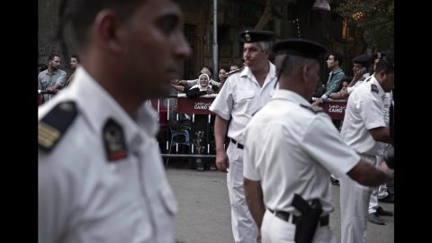 Journalists and spectators wait for ambulances to arrive at the Zeinhom morgue in Cairo on October 31.
