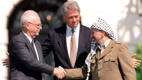 U.S. President Bill Clinton stands between Israeli Prime Minister Yitzhak Rabin, left, and PLO Chairman Yasser Arafat as they shake hands on September 13, 1993.