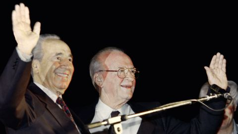 Israeli Foreign Minister Shimon Peres, left, and Prime Minister Yitzhak Rabin wave to the crowd at the peace rally in Tel Aviv on November 4, 1995.