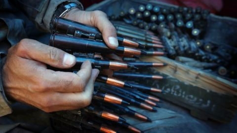 An Iraqi Kurdish Peshmerga fighter prepares an ammunition belt as he guards a position at the frontline of fighting against ISIS militants near the northern Iraqi town of Sinjar.