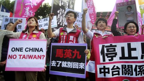 """Opposition protesters shout slogans with placards opposing the planned meeting of Taiwan's President Ma Ying-jeou with his China counterpart Xi Jinping in Taipei, Taiwan, Wednesday, Nov. 4, 2015. Taiwan's President Ma and China President Xi will meet in Singapore, Saturday, Nov. 7, 2015, for the first time since civil war divided their lands 66 years ago, their governments said Wednesday, a highly symbolic move that reflects quickly improving relations between the formerly bitter Cold War foes. Placards read """"Don't Come Back If You Go"""" and """"Stop China-Taiwan Relationship"""". (AP Photo/Chiang Ying-ying)"""