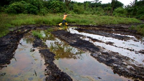 A man jumps across water dirtied by oil pollution in Ogoniland, Nigeria.