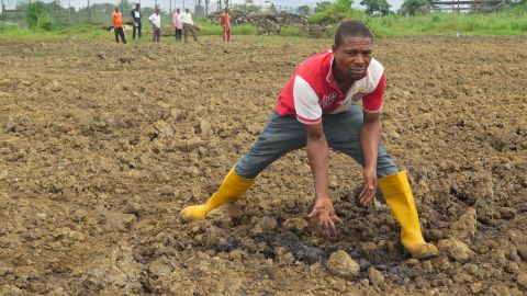 A man shows how the land is contaminated with oil pollution.