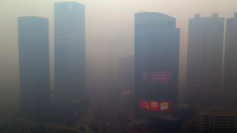 This picture taken on November 8, 2015 shows a residential block covered in smog in Shenyang, China's Liaoning province.  A swathe of China was blanketed with dangerous acrid smog after levels of the most dangerous particulates reached almost 50 times World Health Organization maximums.