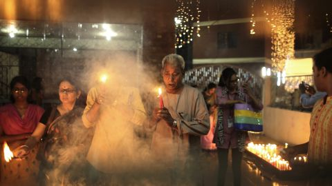 Men and women light candles at a temple in Dhaka, Bangladesh, on November 10.