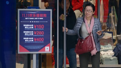 """A woman walks out a shop past a """"Singles Day"""" sales promotional board in Beijing on November 11, 2015.  Shoppers spent around 9 billion USD in the first 12 hours of China's """"Singles Day"""" sale on November 11, e-commerce giant Alibaba said, in the world's biggest online shopping day.         AFP PHOTO / WANG ZHAO        (Photo credit should read WANG ZHAO/AFP/Getty Images)"""