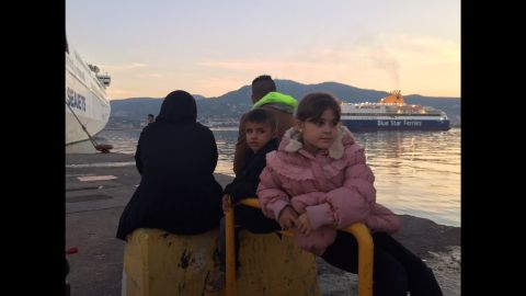 """Farah (R), 10, is from Baghdad. She has been waiting with her younger brother and parents for a boat to Athens for two days. When asked why they are leaving, she says, """"the situation in Baghdad is not good, that's what daddy said."""""""