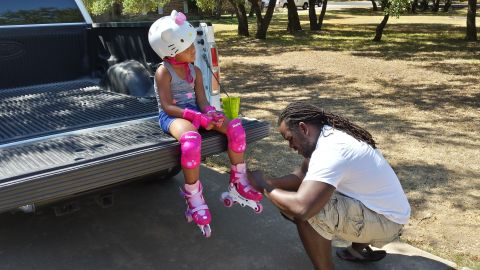 Kaylee got new skates for her birthday and Chris is helping her put them on in this photo.