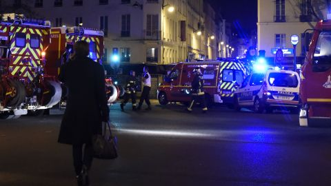 A woman walks past police and firefighters in the Oberkampf area of Paris.