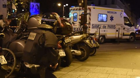 A riot police officer stands by an ambulance near the Bataclan concert hall in central Paris.