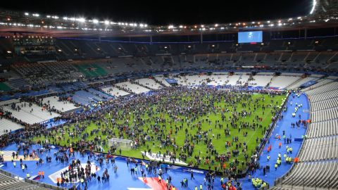 Spectators gather on the field of the Stade de France after the attacks. Explosions were heard during the soccer match between France and Germany.