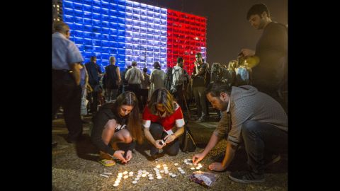 People in Tel Aviv, Israel, light candles and hold posters during a gathering to honor the victims of the Paris attacks on November 14.