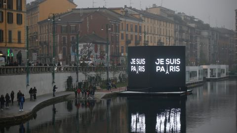 """An electronic billboard on a canal in Milan, Italy reads, in French, """"I'm Paris,"""" on November 14."""