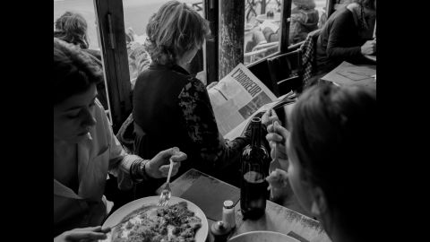 """A woman reads a publication with bolded and capitalized letters spelling out l'horreur, while people all around her fork pieces of food from their plates. """"People were standing outside, having their brunch or whatever, and literally 100 meters away, eight hours before, 18 people (were) being killed,"""" Majoli said.<br />"""