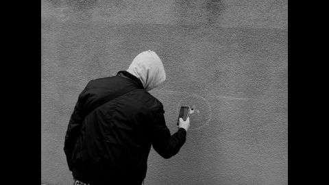 """A man uses his phone to take a photo of a bullet hole near Le Carillon and Le Petit Cambodge. The photographer says he tries to capture the theatrical side of life, using light in a way that """"creates this idea of fiction, of theater.""""<br />"""