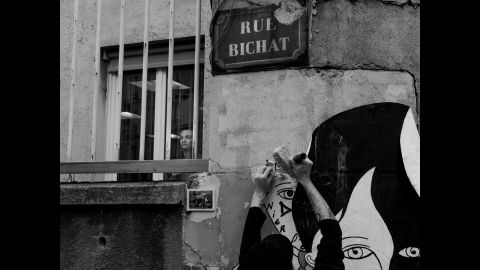 A man looks out the window of a building on Rue Bichat as someone pastes an image onto the wall outside.