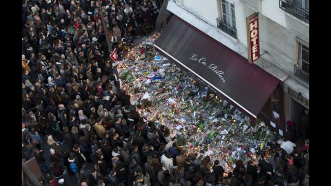 A large crowd gathers to lay flowers and candles in front of the Carillon restaurant in Paris on Sunday, November 15.