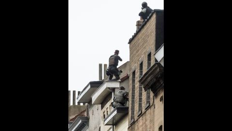 Special forces sit on a roof in Molenbeek as they prepare to enter a house on November 16.