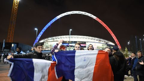 Fans pose in front of Wembley's Stadium arch, which is lit up in the French flag's colors, ahead of the international friendly between England and France Tuesday. Security in London has been tightened after a series of terror attacks across the French capital of Paris Friday, leaving at least 129 people dead and hundreds more injured.
