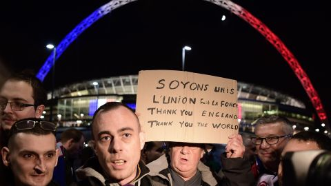 Football supporters holding a message of thanks are interviewed by the media outside Wembley Stadium.