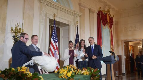 Obama and his daughters, Sasha and Malia, applaud Cheese, the national Thanksgiving turkey, in 2014.
