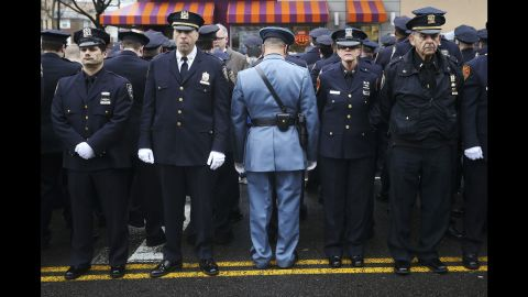 """<strong>January 4: </strong>Law enforcement officers stand outside <a href=""""http://www.cnn.com/2015/01/04/us/gallery/liu-funeral/index.html"""" target=""""_blank"""">the funeral of fallen New York police officer Wenjian Liu.</a> Some officers turned their backs while New York Mayor Bill de Blasio spoke on a monitor. <a href=""""http://www.cnn.com/2014/12/22/politics/de-blasio-police-shooting/index.html"""" target=""""_blank"""">The mayor's critics</a> believed his comments after the death of Eric Garner contributed to an anti-police sentiment that led to the shootings of Liu and his partner, Rafael Ramos."""
