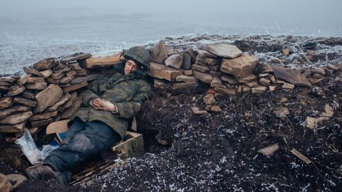 """<strong>February 15:</strong> A pro-Russian rebel rests in Debaltseve, Ukraine, one day after a skirmish with Ukrainian troops. <a href=""""http://www.cnn.com/2015/03/02/europe/ukraine-death-toll/"""" target=""""_blank"""">Fighting between Ukrainian troops and pro-Russian rebels</a> has left more than 6,000 people dead since April 2014, according to the United Nations. A recent ceasefire, the so-called Minsk Agreement, has been repeatedly violated."""