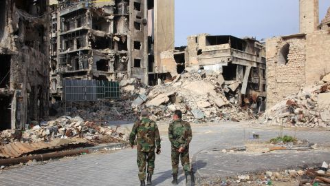 Syrian government forces walk on a heavily damaged street in the regime-controlled side of the northern city of Aleppo on November 9.