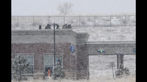 Police sit on the roof of a Chase Bank branch across the parking lot from the scene at Fillmore Street and Centennial Boulevard.