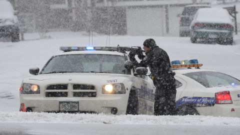 An officer waits at an intersection near the scene of a shooting.