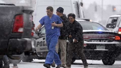 Rescued people are escorted from the area by emergency personnel.