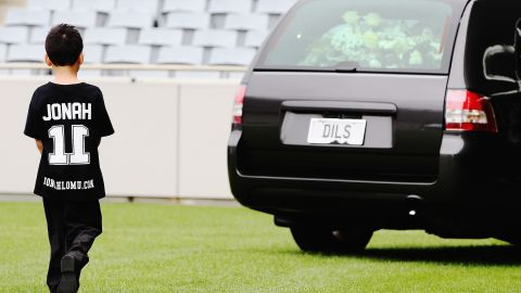 Lomu's son Dhyreille follows the hearse carrying his late father as it leaves the stadium.