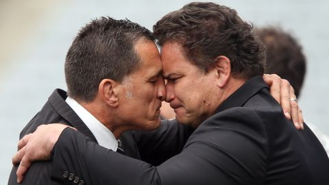 """Former All Blacks Dalls Seymour (L) and Michael Jones perform a traditional Maori """"hongi"""" greeting after the memorial service."""